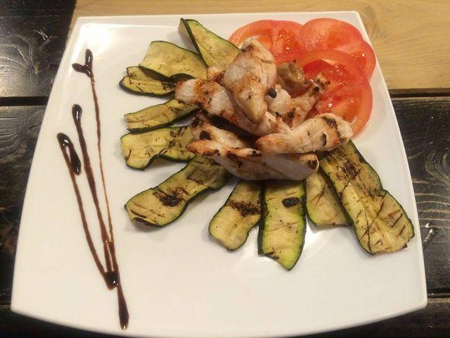 piatto di carne con zucchine grigliate e pomodori