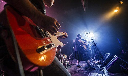 vista laterale di un gruppo musicale che sta suonando su un palco con luci blu