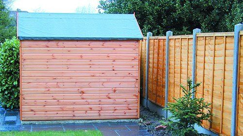 A garden shed with a turquoise roof, in front of a timber fence with posts of the same colour as the shed roof