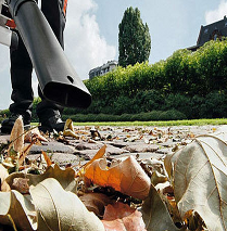 A leaf-blower being used on Autumn leaves in a garden