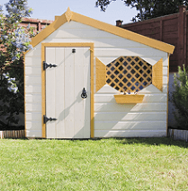 A pretty white garden shed with a lattice shuttered window and cream frames and fascias