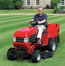 A man mowing a large lawn in stripes, on a red ride-on mower