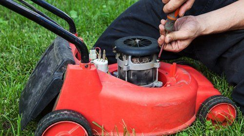 A red motor mower being topped up with oil
