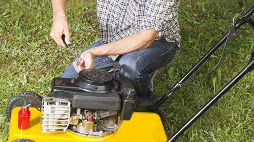 A man in a check shirt and jeans repairing a yellow mower