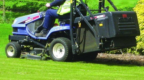 A man on a blue ride-on mower