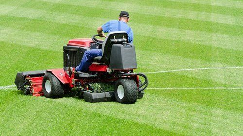 A man on a ride-on mower, mowing a lawn in