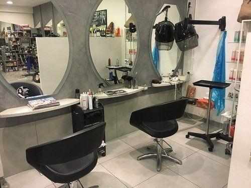 postazione del parrucchiere con due sedie di pelle davanti agli specchi