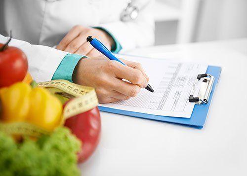 Medico che prescrive una dieta. Cibo salutare sulla scrivania