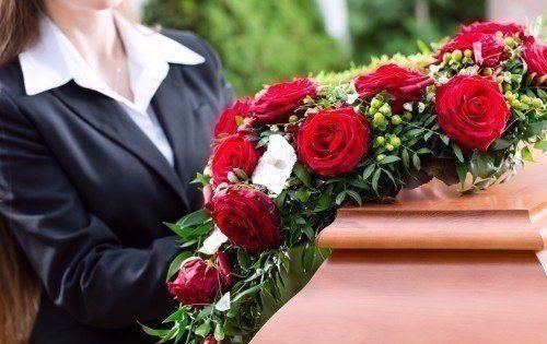 Donna mettendo di fiori rossi sulla bara