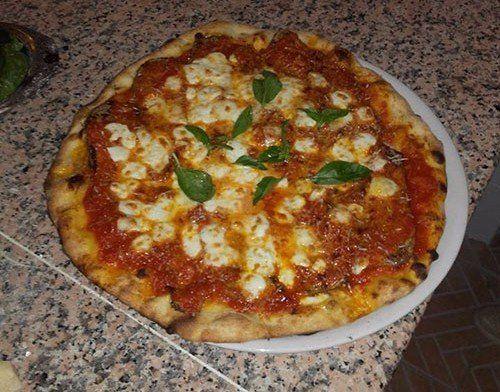 una pizza margherita con delle foglie di basilico