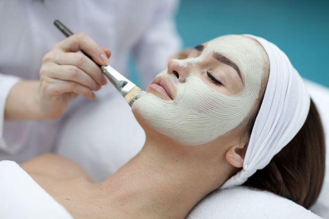 una donna sdraiata con una fascia in testa e un estetista con in mano un  pennello che le applica una maschera con una crema bianca