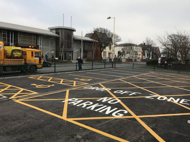 car park markings in white and yellow thermoplastic