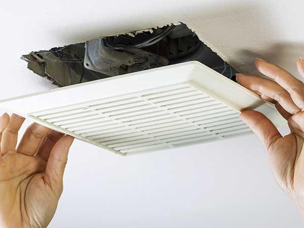 due mani che installano una griglia su un soffitto