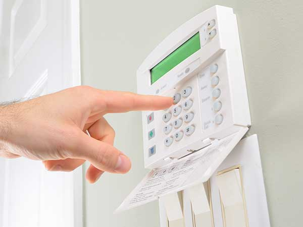 un dito che digita dei tasti di un impianto di sicurezza