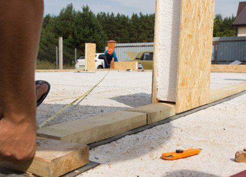 Due operai misurano la base di una struttura