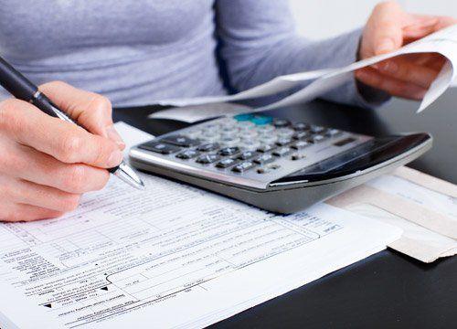 Donna scrive sui documenti usando la calcolatrice