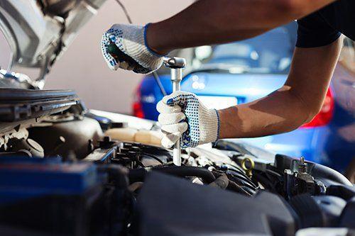 meccanico mentre avvita una parte del motore di un  auto