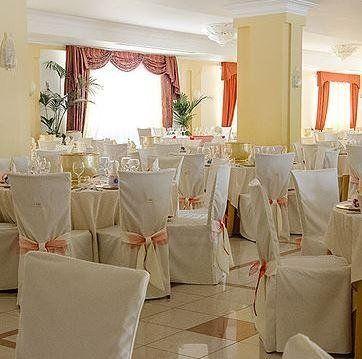 vista interna di un albergo con sedie e tavoli apparecchiati