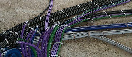 dei cavi elettrici di diversi colori che fuori escono da un muro