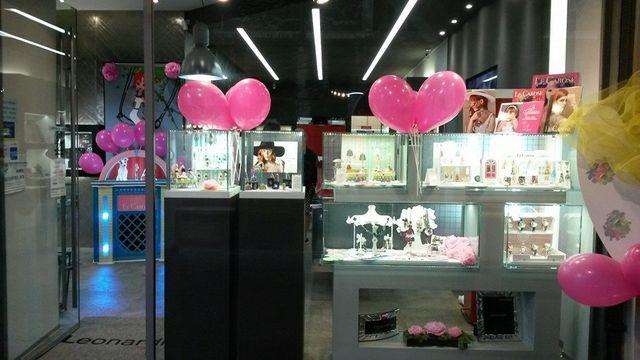 delle vetrine con dei gioielli esposti e di palloncini rosa a forma di cuore