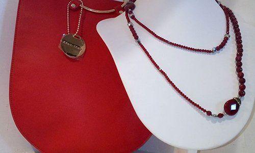 una collana con delle pietre di color rosso e bordeaux