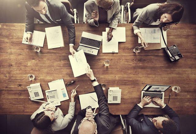 vista dall'alto di persone alla scrivania che lavorano con dei computer, dei documenti e dei telefoni