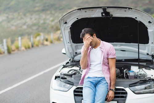 annoyed driver leaning against broken down car with bonnet raised