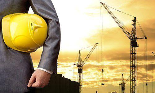 Ingegnere che tiene casco giallo per la sicurezza dei lavoratori