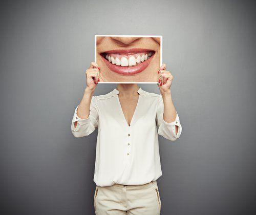 donna con un poster di una bocca che sorride davanti alla faccia