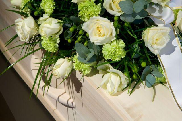una bara in legno con sopra delle rose bianche