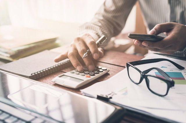 Documenti, occhiali, calcolatrice e cellulare in mano