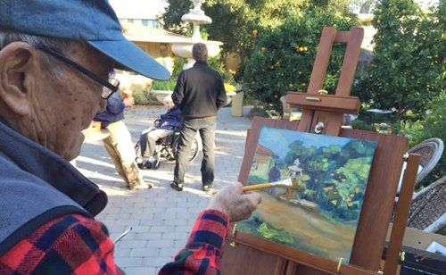 Old man doing painting in open