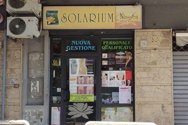 Vista dall'esterno del Solarium Ninfea con un' insegna gialla una porta in vetro e sulla sinistra due motori di alcuni condizionatori
