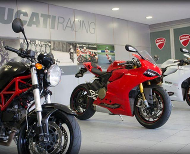 tre moto Ducati una nera, una rossa e una bianca in esposizione in uno showroom Ducati Racing