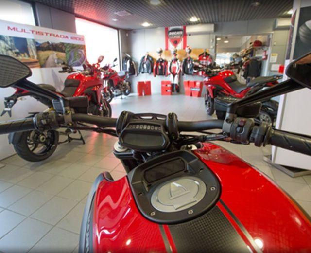 vista dal manubrio di una Ducati rossa e davanti altre moto e giubbotti di pelle Ducati appesi