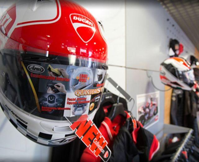 Un casco rosso integrale Ducati e affianco dei giubbotti e altri caschi