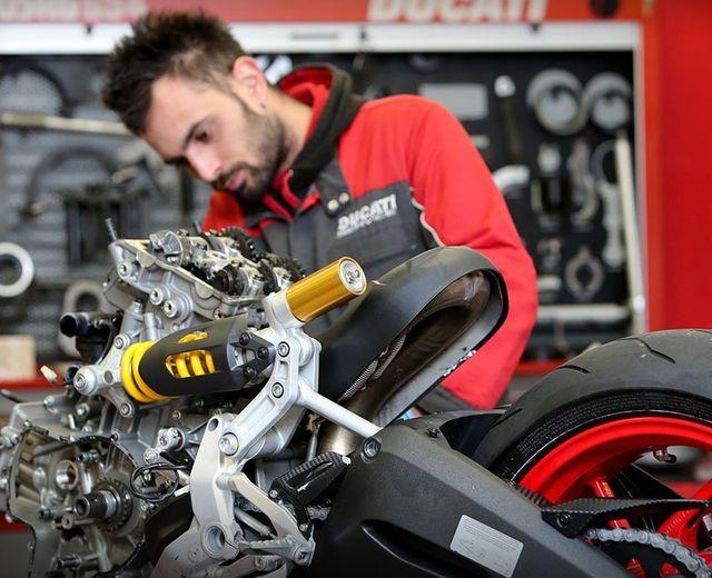 un meccanico Ducati sta sistemando una moto con il davanti smontato