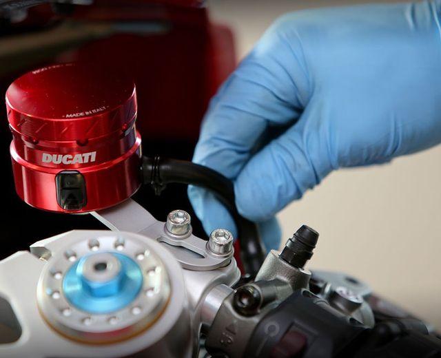 una mano con un guanto in lattice azzurro che sta sistemando dei componenti di una moto Ducati