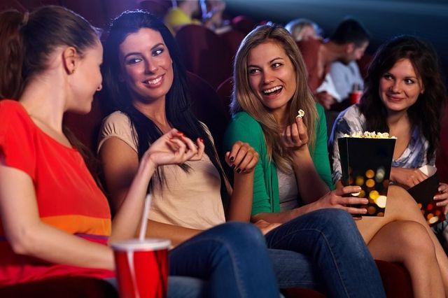 Belle ragazze si siede nella sala del cinema, parlare, sorridere, mangiare popcorn