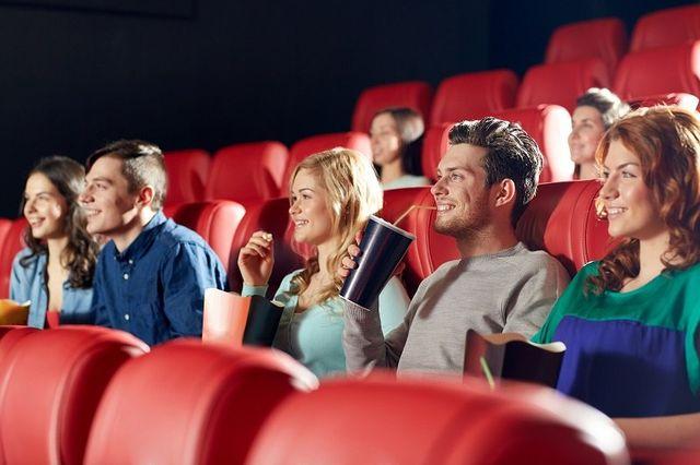 amici felici a guardare film in teatro