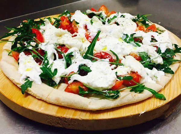 Pizza bianca di pomodori, rucola e mozzarella di bufala