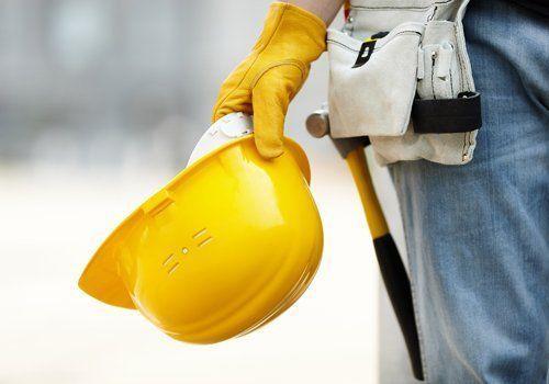 Casco di protezione nel mano di un'operaio