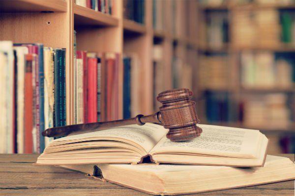 il martello  della giustizia su alcuni libri in una  stanza piena di scaffali con libri