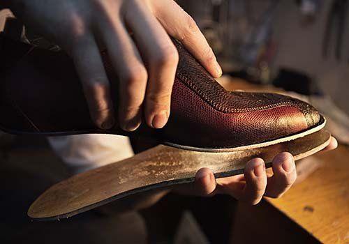 Artigiano incolla la suola alla tomaia di una scarpa da uomo