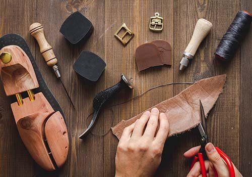 Artigiano taglia la pelle necessaria alla manifattura della scarpa le cui parti sono ancora da assemblare