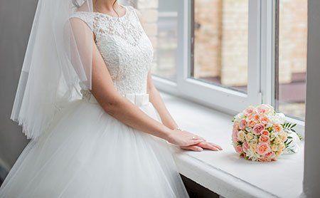 una sposa davanti  una finestra e un bouquet di fiori