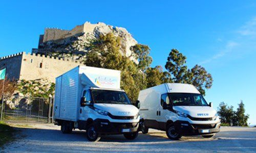 due furgoni bianchi e un castello nello sfondo