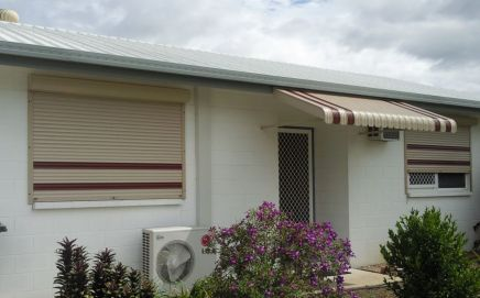 house with screen door and roller shutters with awning