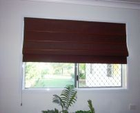 red roman blinds over window