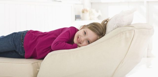 Girl lays on sofa after upholstery cleaning in Palmerston North